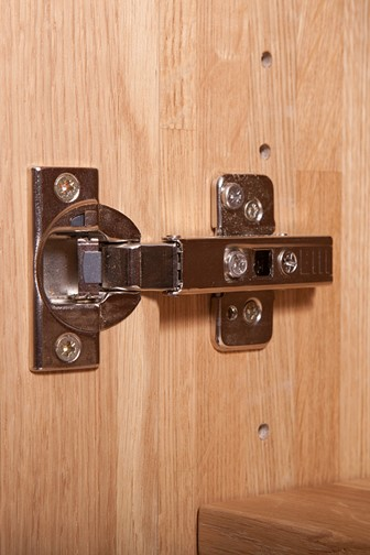 cupboard door hinge on a wooden cabinet